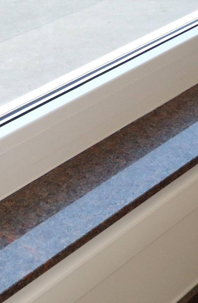 Okenska polica iz temno-rjavega naravnega kamna z odsevom naravne svetlobe.