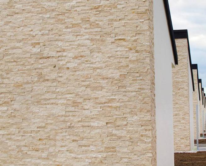 Kamnite obloge iz naravnega kamna, svetle barve na fasadi hiše.