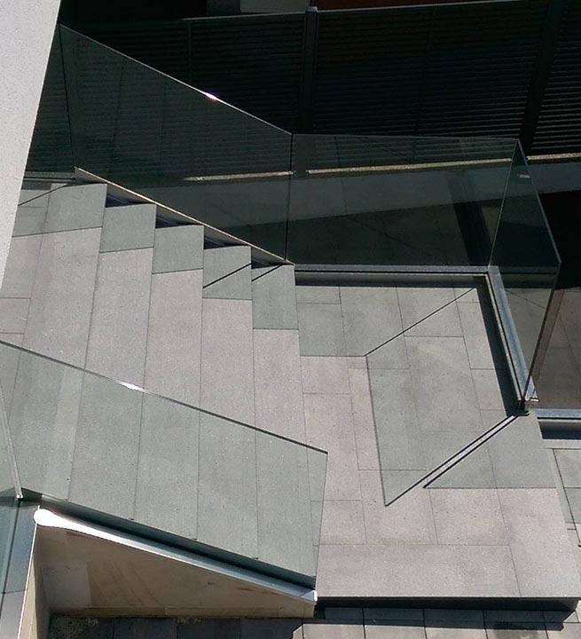 Stopnice iz naravnega kamna, obdane s stekleno ograjo.